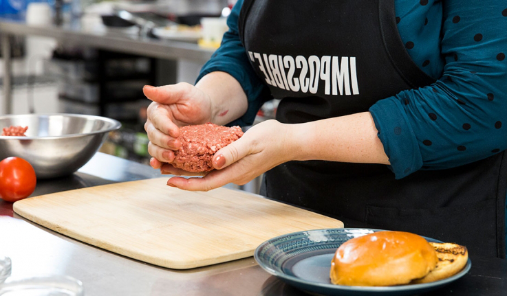 "A woman creates a ball of ""impossible burger."""